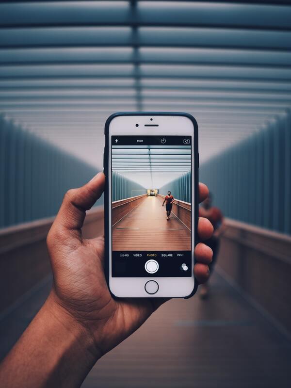 foto da tela do celular tirando foto de uma mulher em um corredor vazio
