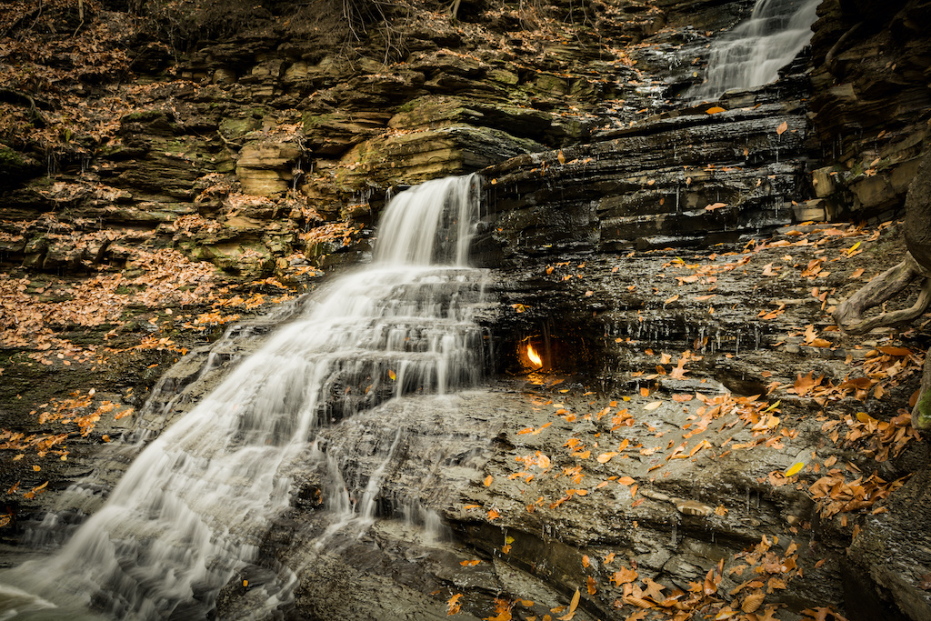 Eternal Flame behind a waterfall with leaves falling around it