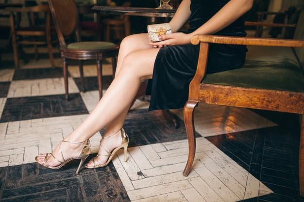 Long skinny legs wearing high heeled sandals shoes, fashion details of elegant beautiful woman sitting in vintage cafe in black velvet dress, rich stylish lady, elegant trend footwear Free Photo