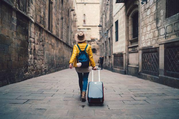 Женщина с чемоданом на улице Барселоны