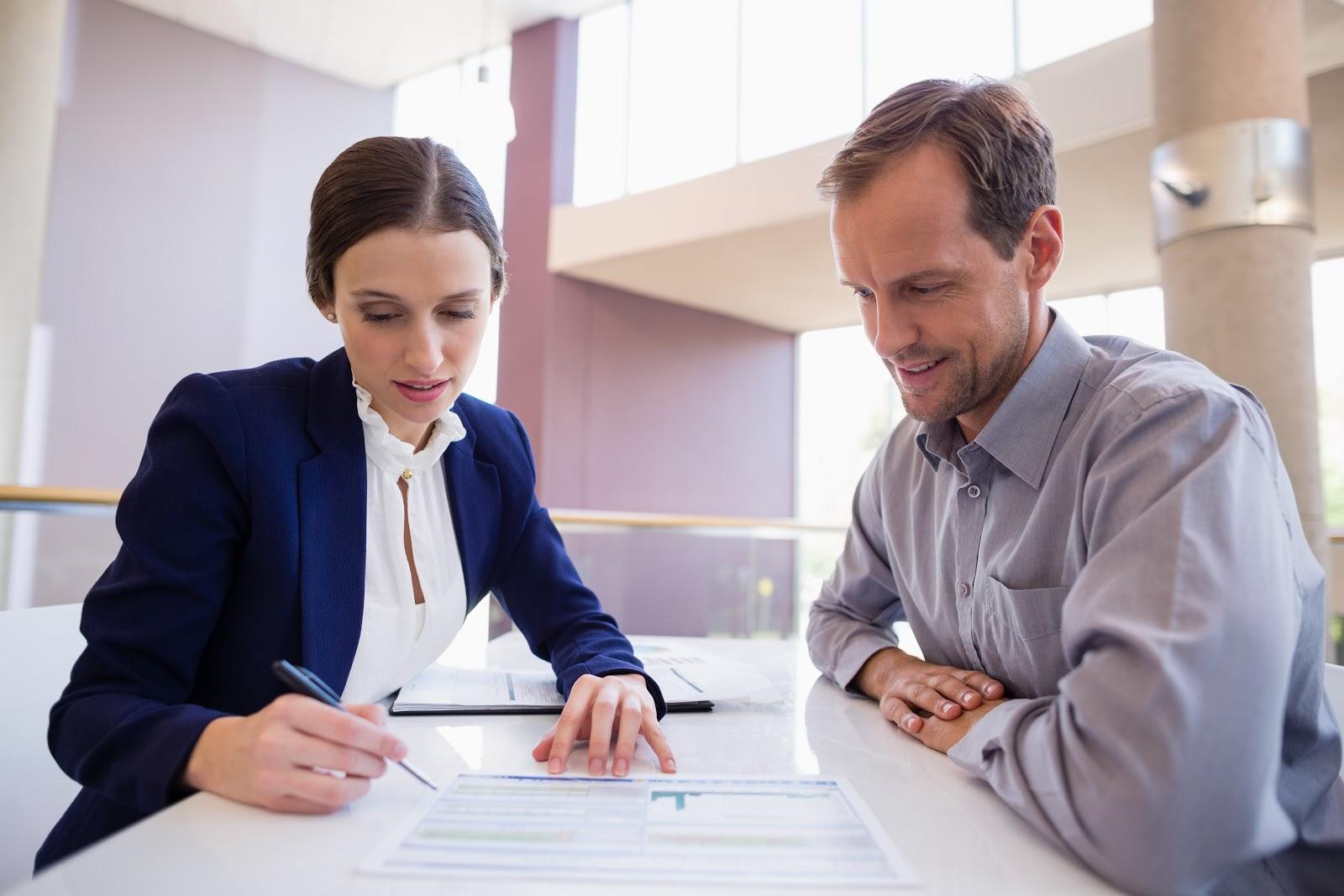 Duas pessoas olhando para um papel em uma mesa.