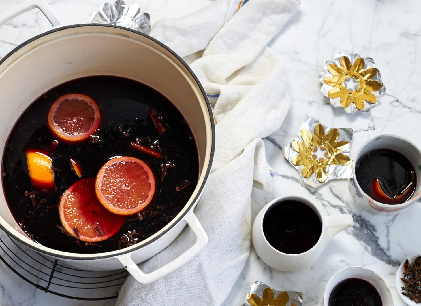 Pot filled with hot gluhwein & sliced oranges next to mugs filled with gluhwein