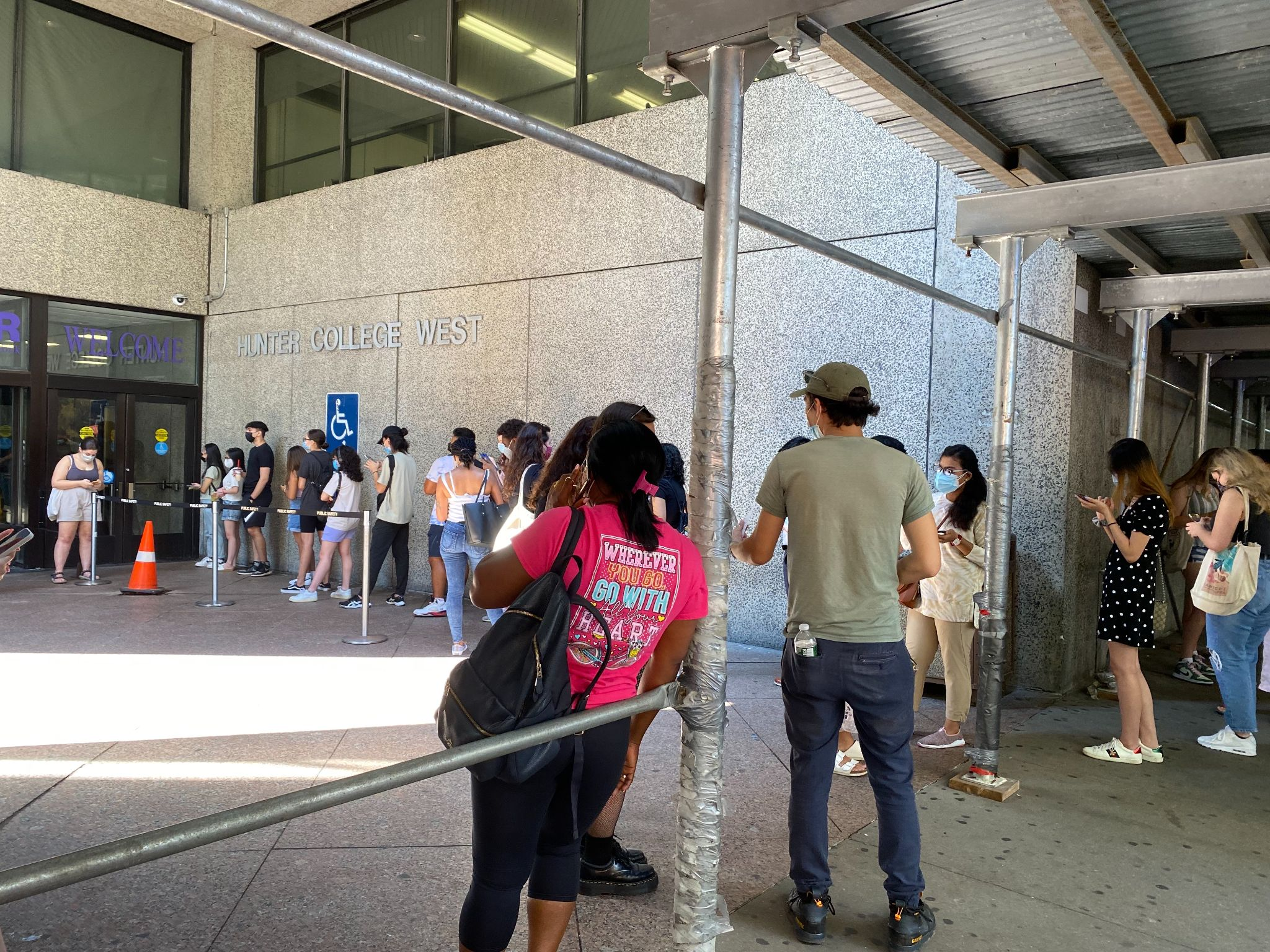 The image shows unvaccinated students waiting on a line outside Hunter's West Building.