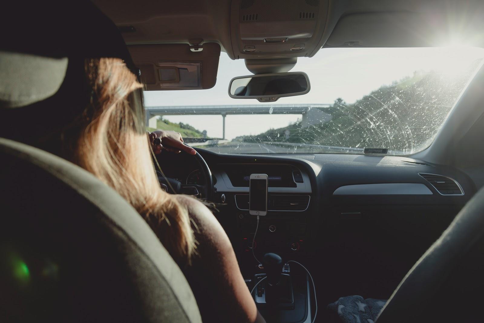 Mulher motorista de aplicativo dirigindo com as mãos no volanete e celular ao lado.