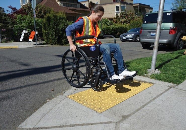 Picture: A person in a wheelchair utilizes an accessibility ramp on a sidewalk.