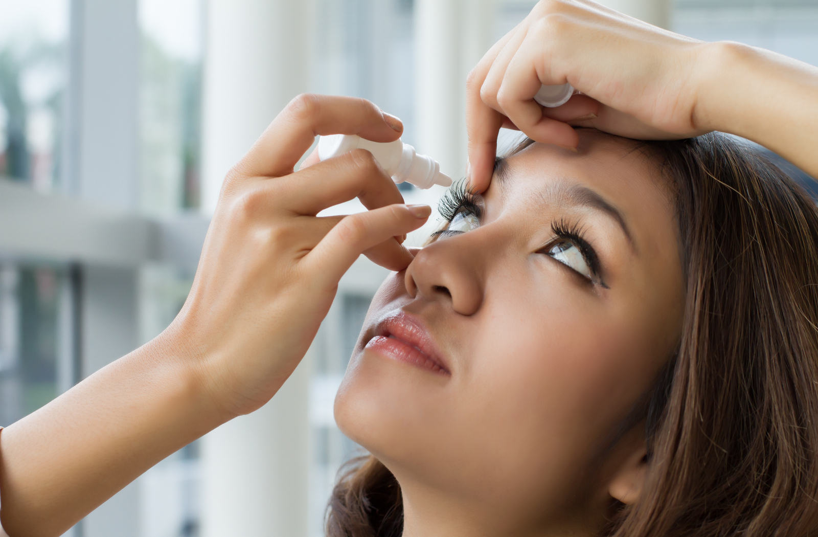 a woman of asian descent administering eye drops into her right eye