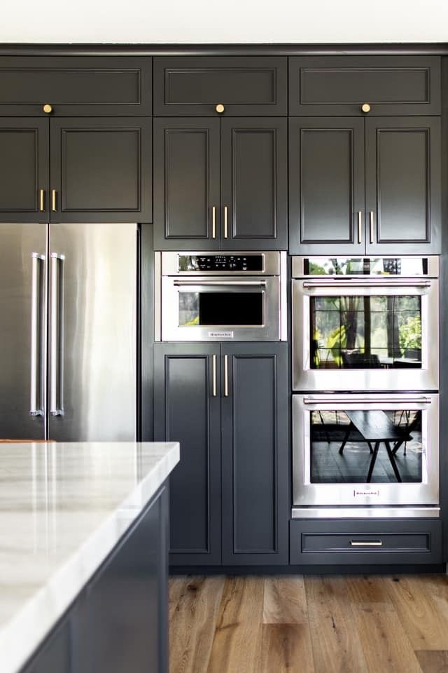 dark shaker cabinets with stainless steel appliances and matching cabinet hardware