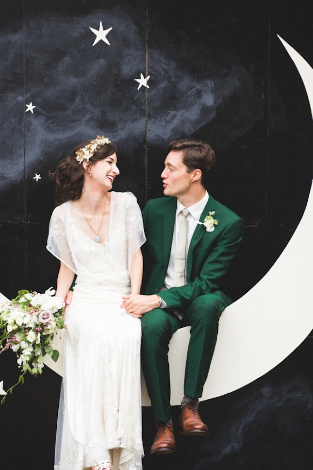 Wedding couple sitting on a paper moon