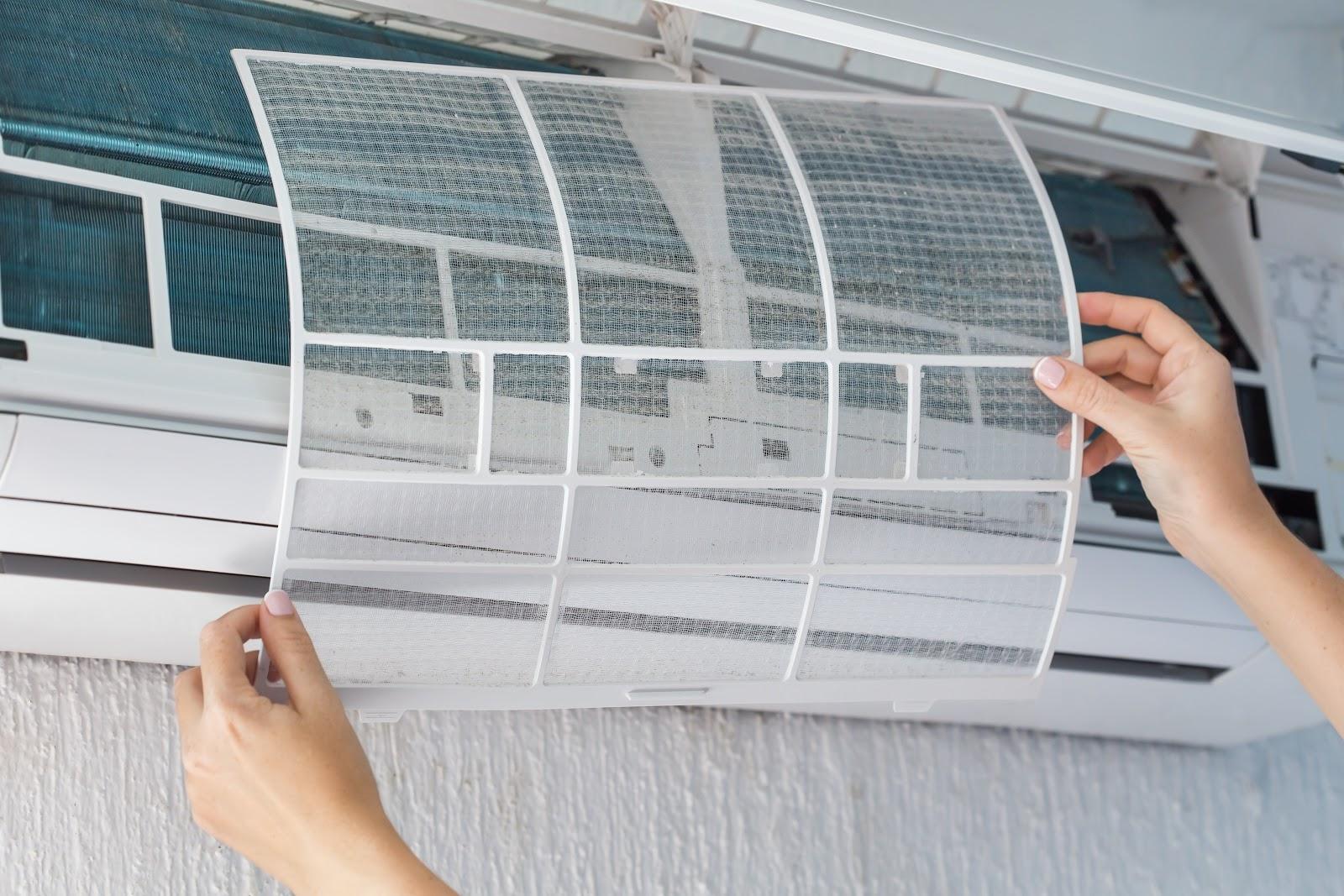 Uma pessoa segurando uma peça interna de um ar condicionado.