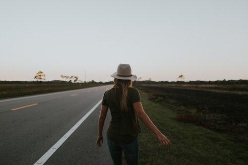 person walking alongside road