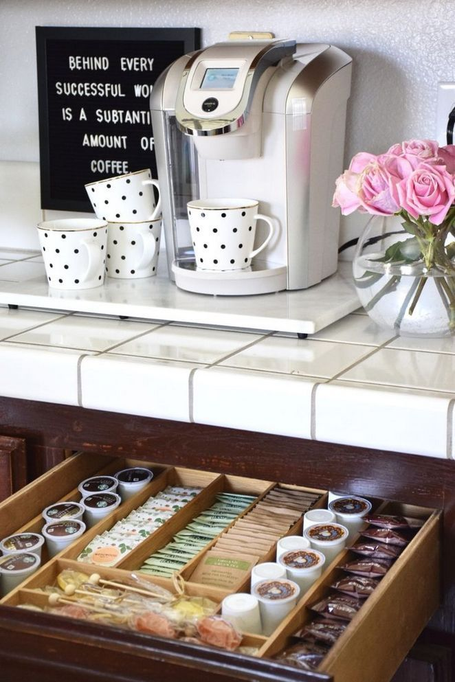 white countertops with a white keurig and mugs on top. sitting above a pull out drawer with a k-cup insert