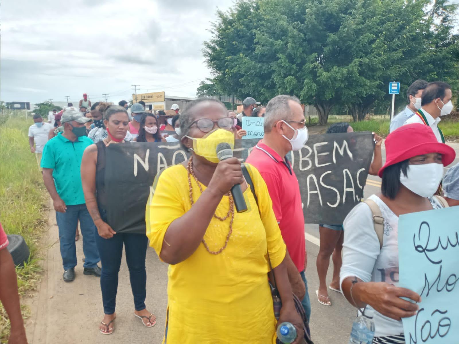 Dona Mira Alves, mulher negra, de máscara e roupa amarela, numa manifestação de rua em defesa de moradia em Santo Antônio de Jesus