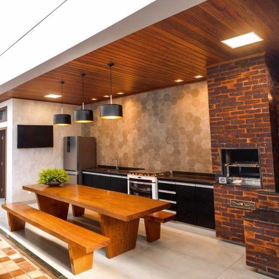 Espaço com churrasqueiro de tijolinhos escuro, pia e bancada com granito preto, revestimento hexagonal na parede, mesa e bancos de madeira, teto revestido de madeira e piso porcelanato branco.