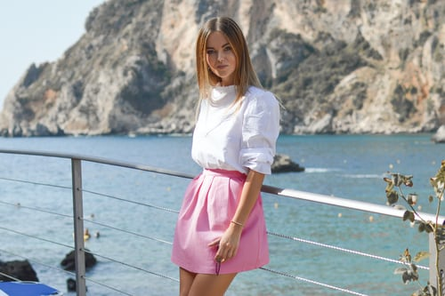 A view from the ocean with the woman in pink skirt and white top.