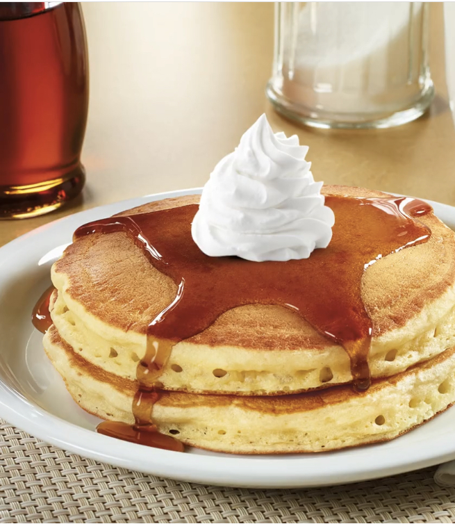 Pancake stack with syrup and whipped cream from Denny's