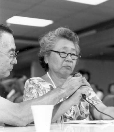 Martha Okamoto speaking into a microphone at a CWRIC hearing in Los Angeles. She has a pained expression, and a man seated next to her is assisting her with the microphone.