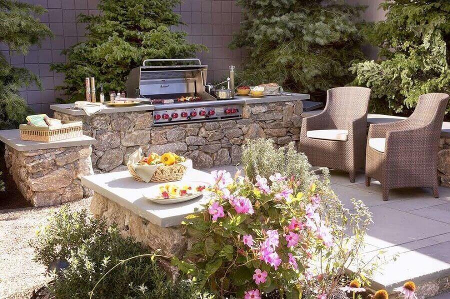 Ambiente externo com muitas plantas, churrasqueira elétrica sob muro de pedras e poltronas.