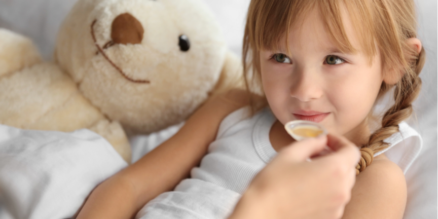 young-girl-in-bed-being-given-a-spoonful-of-medicine