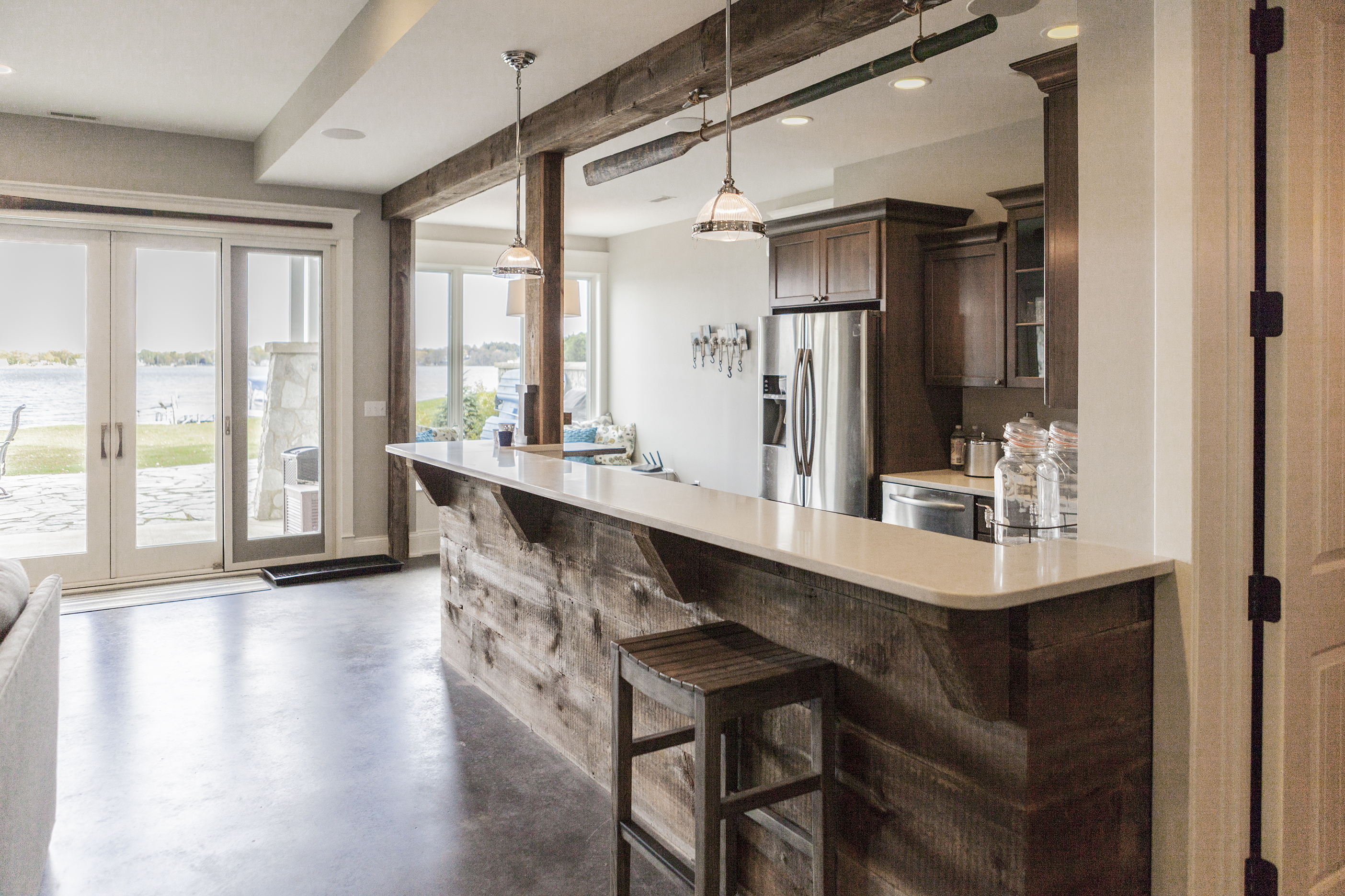 Walk-out basement bar with a wood plank bar topped by white quartz countertops.