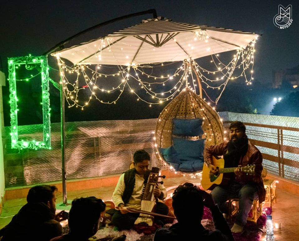 People sitting on the terrace surrounded by fairy lights, enjoying themselves as two male artists play guitar and violin respectively.
