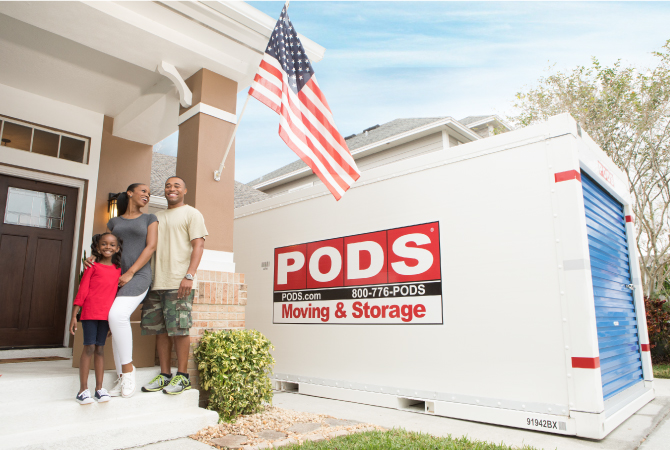 A family standing in front of their home near their PODS storage container.