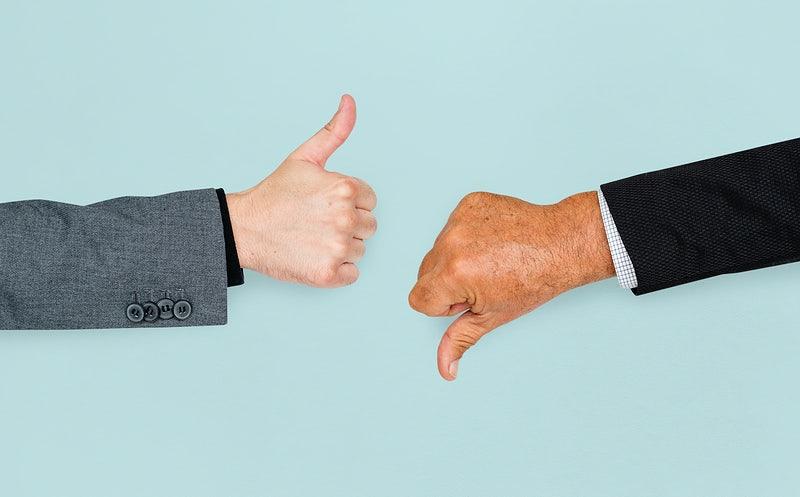 Duas mãos fazendo símbolos de aprovação e reprovação.