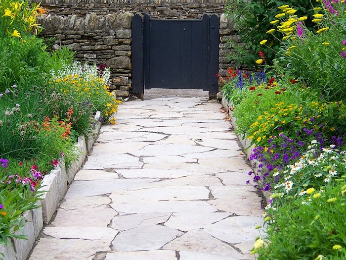 A sidewalk made of landscaping stones surrounded by bright colorful flowers and greenery leading up to a black gate.