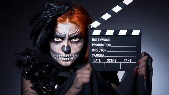 Goth woman with red hair holding a movie action board.