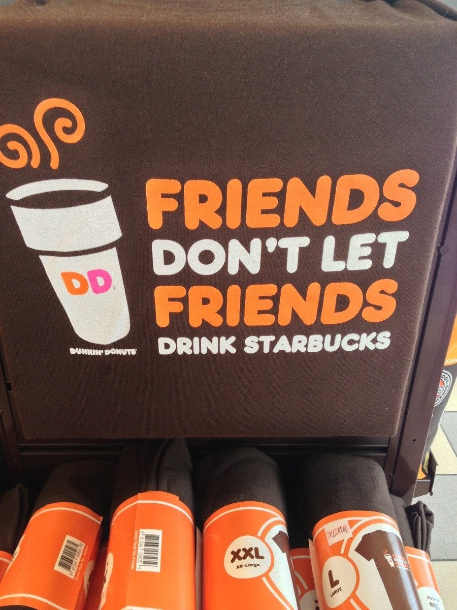 """Dunkin Donuts' T-shirt merch with the text """"Friends don't let friends drink Starbucks"""""""