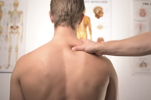 Massage therapist pressing onto trigger point to treat patient