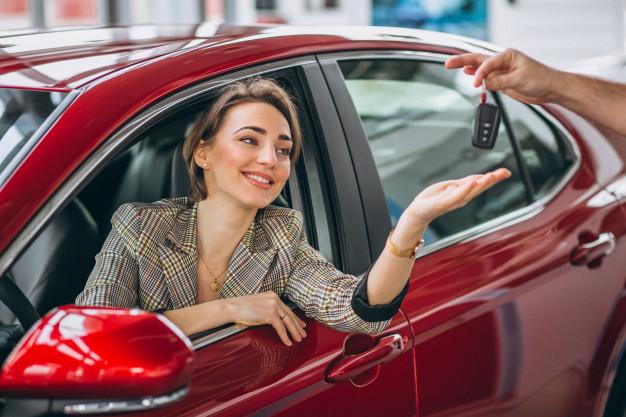 Mulher motorista dentro do carro estendendo a mão para pegar a chave após o aluguel de carros para 99.