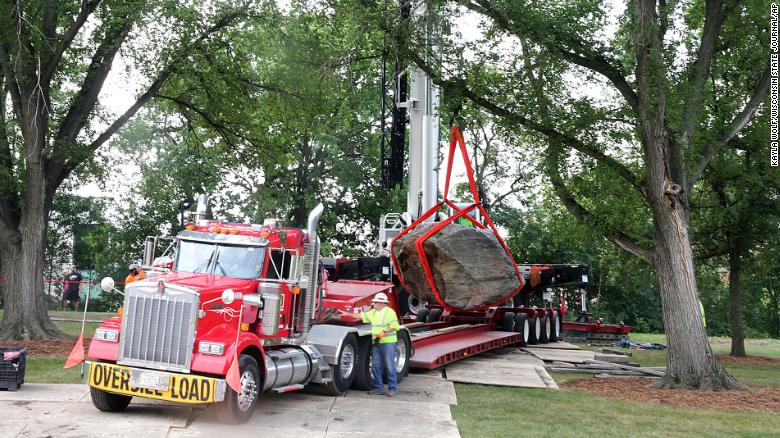 A crane operator slowly maneuvers Chamberlin Rock onto a flatbed trailer on campus on Friday.