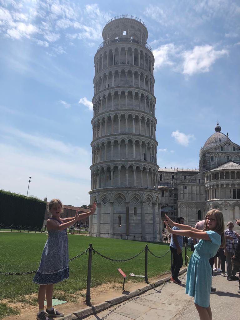 zwei Kinder halten den Turm von Pisa fest