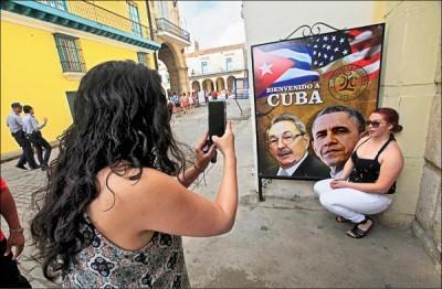 美國總統歐巴馬二十日抵達古巴訪問,古巴首都哈瓦那街頭十九日已出現不少歡迎歐巴馬來訪的標語,圖為一名來自加州的觀光客,與印有歐巴馬和古巴總統勞爾.卡斯楚肖像的海報合影。 (路透)