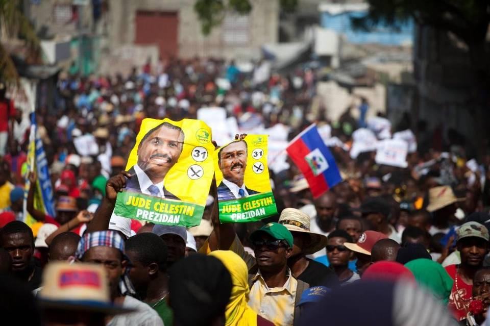 Protesters hold up election posters promoting presidential candidate Jude Celestin of the Lapeh party, during a protest against official preliminary election results, in Port-au-Prince, Haiti, Wednesday, Nov. 11, 2015. Haitian political parties Lavalas, Lapeh, and Platform Pitit Dessalines, have joined to demand the cancellation of the recent presidential election, or removal of ruling party candidate Jovenel Moise who is set to face Celestin in the Dec. 27 presidential runoff election.