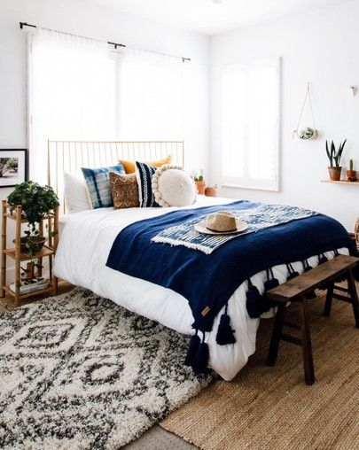 white bedroom decoration with a dark blue throw blanket