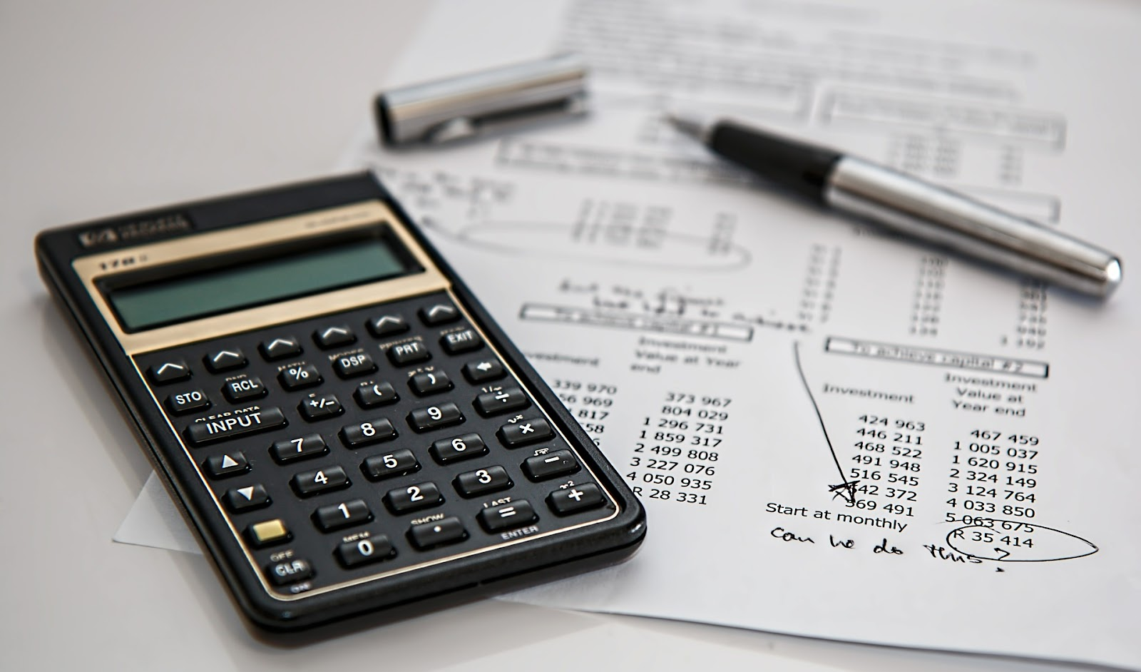 A calculator placed on a desk on top of an accounting paper Coding Bootcamp Scholarships
