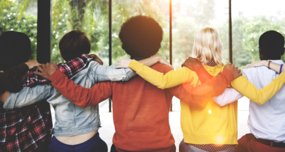 A group of friends with their arms over each other's shoulders