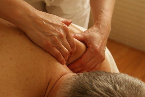 Person Massaging Man's Shoulder