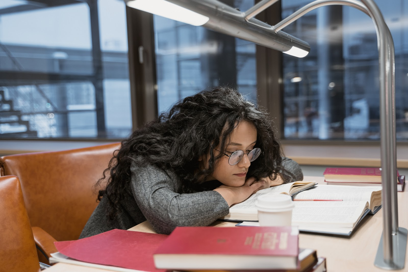 A teen girl wearing glasses is reading over multiple textbooks with a cup of coffee on the table.