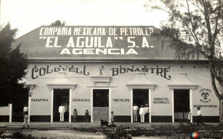Edificio con letrero en frente y tienda al lado  Descripción generada automáticamente