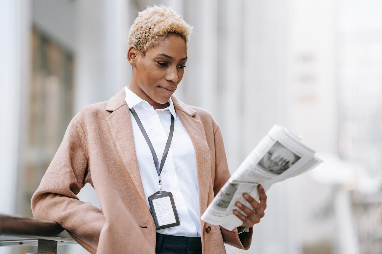 woman in pink blazer reading newspaper