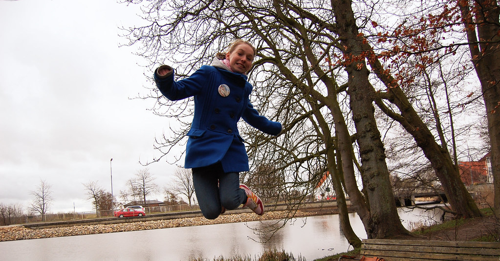 girl jumping next to tree