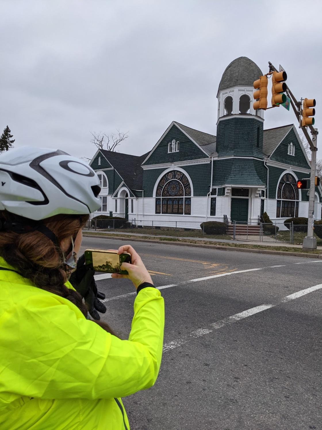 A person wearing a helmet is taking a picture of a green and white church with a big stained glass window.