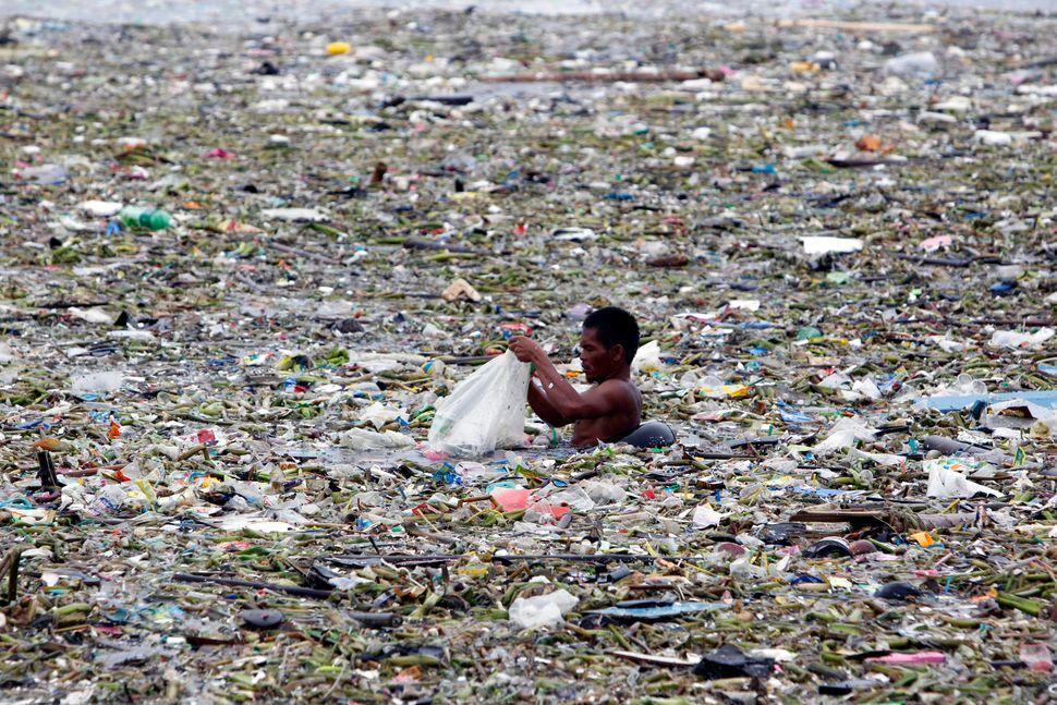 Mężczyzna segregujący śmieci w morzu odpadów