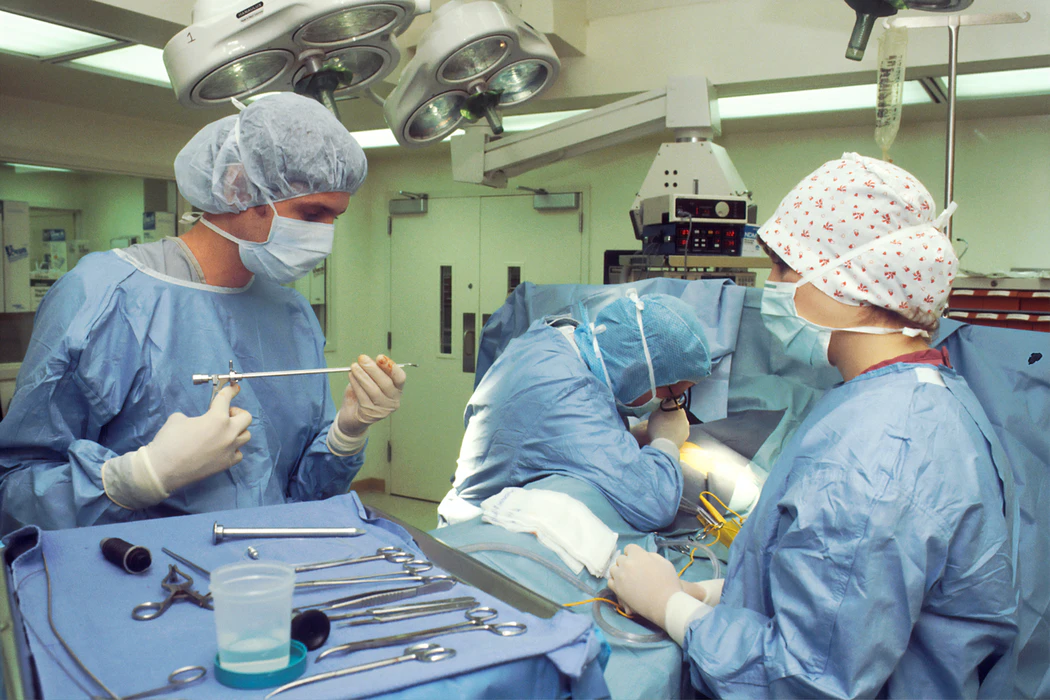 Nurses and doctor in blue scrubs during surgery