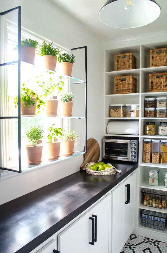 modern black and white pantry design with window and herbs, wicker baskets, black countertops, matte black hardware and white shaker cabinets