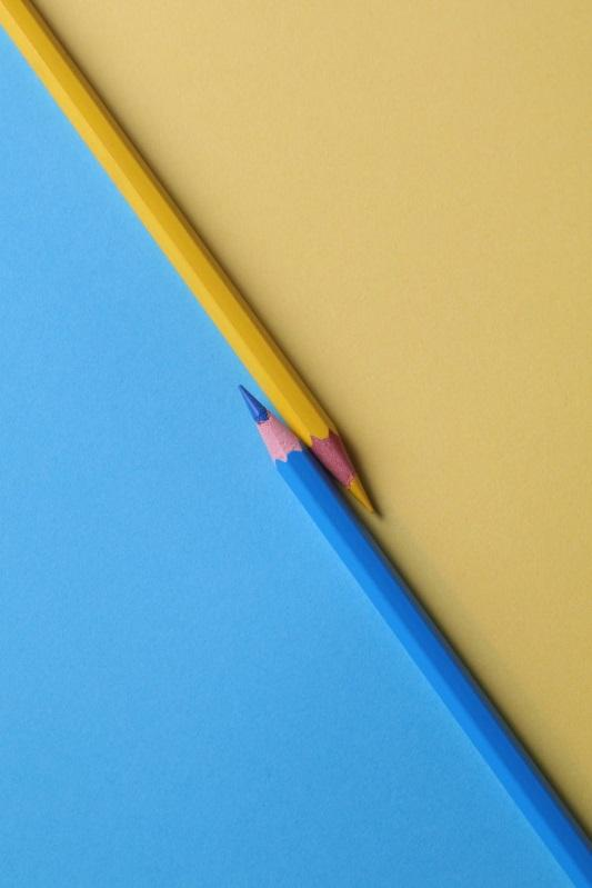 A blue and a yellow pencil separating a blue and yellow background.