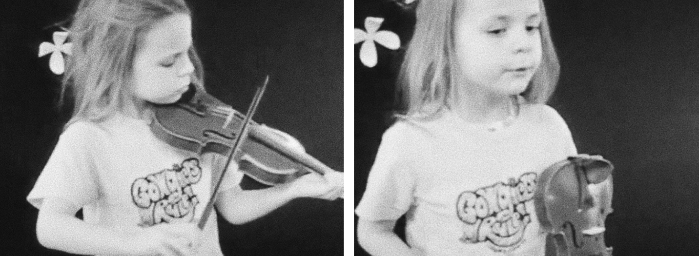 A young Molly, holding and playing a violin