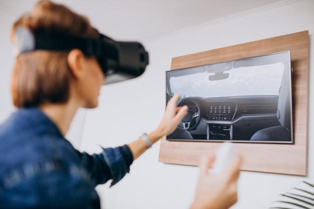 Young woman wearing vr glasses and playing virtual game using remote Free Photo